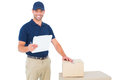 Happy delivery man with cardboard boxes and clipboard Royalty Free Stock Photo