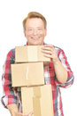 Happy delivery young casually dressed man holding his packages isolated on white focus is on the face Royalty Free Stock Photos