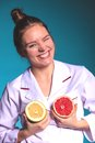 Happy dietitian nutritionist with grapefruit holding having fun woman promoting healthy food fruit right eating nutrition and Stock Photography