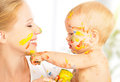 Image : Happy dirty baby draws paints on her face of mother sun female over