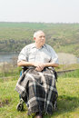 Happy disabled man enjoying the sun senior sitting on a hilltop with scenic views with a blanket over his legs Royalty Free Stock Photography