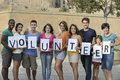 Happy and diverse volunteer group holding sign Stock Images