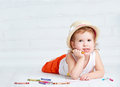 Happy dreamy little artist  girl in a hat draws pencil Royalty Free Stock Photo