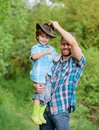 Happy earth day. Eco farm. small boy child help father in farming. father and son in cowboy hat on ranch. kid in rubber Royalty Free Stock Photo