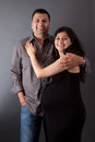 Happy east indian husband with his pregnant wife an men embraces Royalty Free Stock Photos