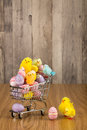 Happy easter chickens shopping cart filled with colored eggs and colored on wooden background Royalty Free Stock Images