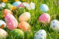 Happy easter!  Closeup Colorful Easter eggs in nest on green grass field during sunset background Royalty Free Stock Photo