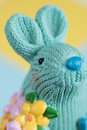 Happy easter concept blue easter bunny with flowers on yellow background close up Royalty Free Stock Photo