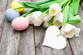 Happy easter eggs and tulips with a tag on wooden background Royalty Free Stock Photo