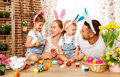 Happy easter! family mother, father and children paint  eggs for Royalty Free Stock Photo