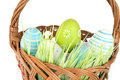 Happy Easter - few eggs on the wooden basket with a grass on the white background