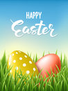 Happy Easter Lettering card decorated gold and red eggs at fresh green grass on blue sky background