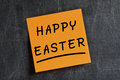 Happy easter post it blackboard handwritten text on orange glued on dirty Royalty Free Stock Image