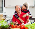 Happy elderly couple cooking in home kitchen with vegetables Royalty Free Stock Photo