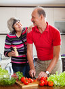 Happy elderly couple cooking lunch veggy in kitchen Royalty Free Stock Photo