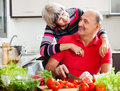 Happy elderly couple cooking with vegetables and greens in home kitchen Royalty Free Stock Photos