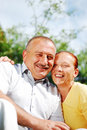Happy elderly couple hugging each other outdoor Stock Photo