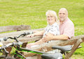 Happy elderly couple relaxing in the park after ride bike Royalty Free Stock Images