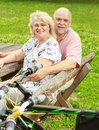 Happy elderly couple relaxing in the park after ride bike Royalty Free Stock Photography