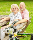 Happy elderly couple relaxing in the park after ride bike Royalty Free Stock Image