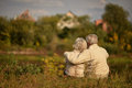 Happy elderly couple sitting embracing in autumn park Royalty Free Stock Photo