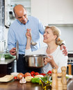 Happy elderly couple smiling and preparing food together in domestic kitchen Royalty Free Stock Photo