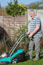 Happy elderly male gardener cutting the grass. Royalty Free Stock Images