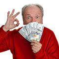 Happy elderly man holding dollar bills and showing ok sign Royalty Free Stock Images
