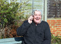 Happy elderly man on a mobile phone. Stock Photography