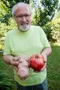 Happy elderly man with potato and tomato Royalty Free Stock Photo