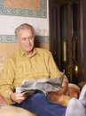 Happy elderly man reading newspaper Royalty Free Stock Image