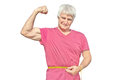 Happy elderly man in red shirt with measuring tape. Elderly man shows own biceps of arm isolated on white background Royalty Free Stock Photo