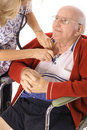 Happy elderly man in wheelchair checking vitals Stock Photos