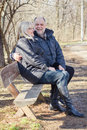 Happy elderly senior couple relaxing in the nature old people sitting on the bench portrait outdoor winter autumn season Royalty Free Stock Images
