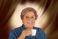 Happy elderly woman drinking coffee on brown background Royalty Free Stock Image