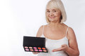 Happy elderly woman using decorative cosmetics Royalty Free Stock Photo