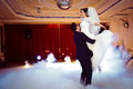 Happy elegant gorgeous married couple performing first dance with heavy smoke and fireworks in a stylish restaurant Royalty Free Stock Photo