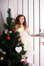 Happy elegant little girl decorating christmas tree smiling and the enjoying the holidays and new year concept Royalty Free Stock Image