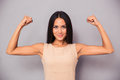 Happy elegant woman showing her biceps portrait of a on gray background Stock Photo