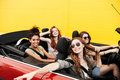 Happy emotional four young women friends sitting in car Royalty Free Stock Photo