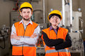 Happy employees in warehouse team of at yellow helmets and vests Royalty Free Stock Images