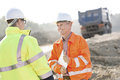 Happy engineer discussing with colleague at construction site on sunny day Stock Images