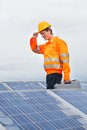 Happy engineer with toolkit standing in front of solar panel Stock Photo