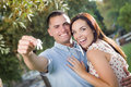 Happy excited couple with new house keys mixed race outside Stock Photos