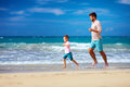 Happy excited father and son running on summer beach enjoy life together Royalty Free Stock Photo