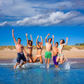 Happy excited teen boys and girls beach jumping group at the splashing water Royalty Free Stock Photo