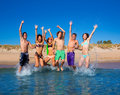 Happy excited teen boys and girls beach jumping group at the splashing water Royalty Free Stock Photography