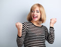 Happy excited winner with opened mouth. Happy blond young satisfacted woman showing the gesture by fists Royalty Free Stock Photo