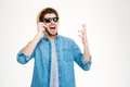 Happy excited young man in sunglasses talking on cell phone Royalty Free Stock Photo