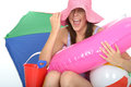 Happy excited young woman on holiday laughing and smiling ecstatic in her twenties wearing a pink sun hat with a pink rubber ring Stock Photography